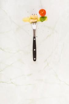 Vista elevada, de, nhoque, macarronada, com, garfo, perto, tomate cereja, e, manjericão, folha