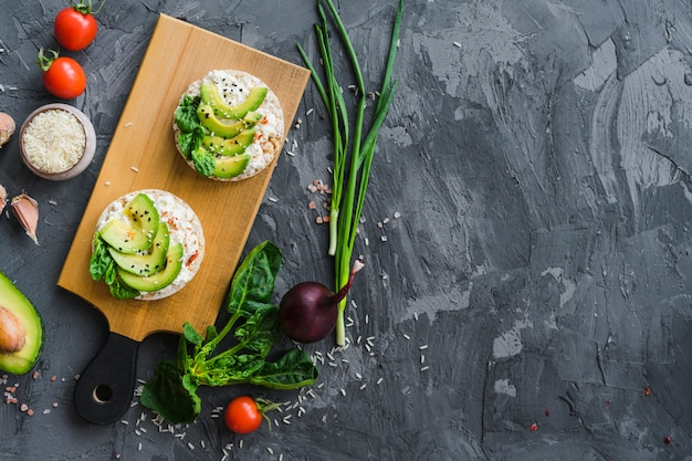 Vista elevada, de, orgânica, legumes, com, saboroso, bolo arroz, refeição, sobre, cinzento, áspero, concreto, fundo