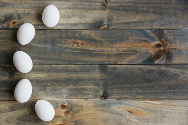 Vista elevada, de, ovos brancos, formando curva, forma, ligado, madeira, fundo