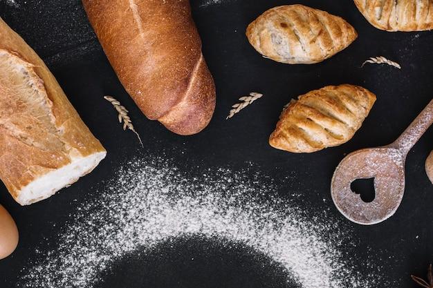 Vista elevada de pães frescos; colher de forma de coração; grão e farinha no fundo preto