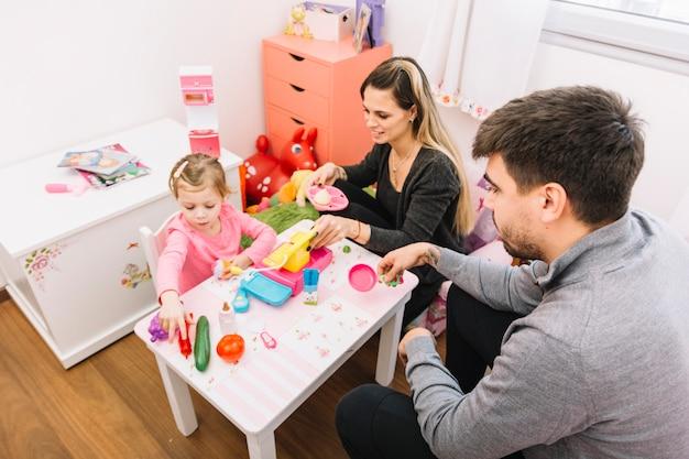 Vista elevada, de, pais, olhar, filha, tocando, brinquedos