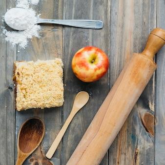 Vista elevada de pastelaria; maçã; farinha; rolo de massa e colher na superfície de madeira