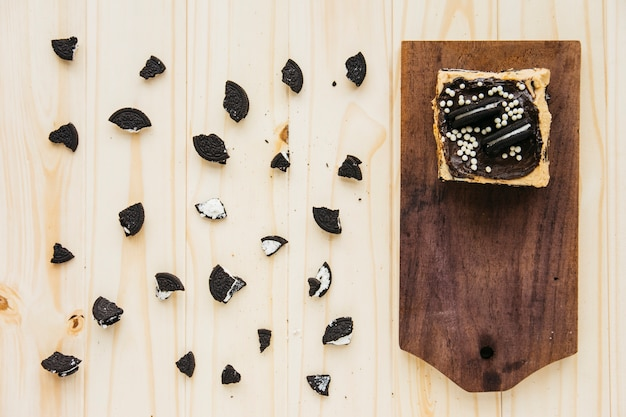 Vista elevada de pastelaria perto de pedaços de cookie em fundo de madeira