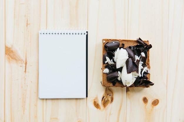 Vista elevada de pastelaria perto do bloco de notas em branco na superfície de madeira