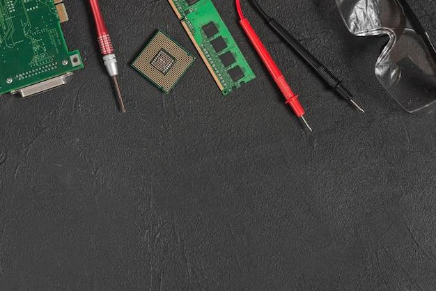 Vista elevada de peças de computador; óculos de segurança e multímetro digital em pano de fundo preto