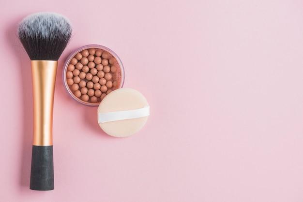 Vista elevada de pérolas bronzeadoras; esponja e pincel de maquiagem no pano de fundo rosa