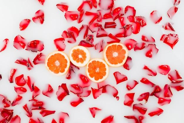 Vista elevada de pétalas de flores e fatias de grapefruit