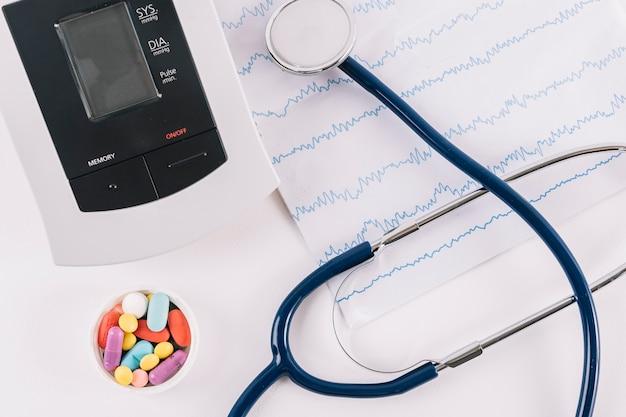 Vista elevada de pílulas; cardiograma; monitor de estetoscópio e pressão arterial