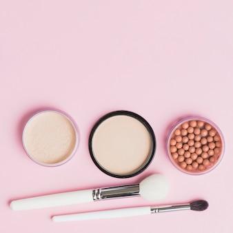 Vista elevada de pós faciais; pérolas bronzeadoras e pincéis de maquiagem em fundo rosa
