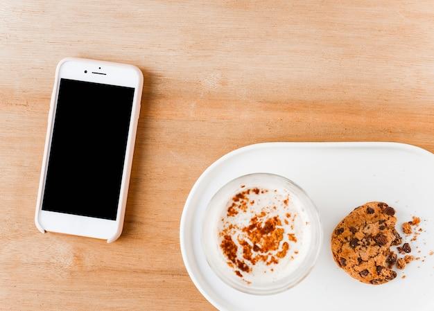 Vista elevada, de, smartphone, com, copo café, e, comido, biscoitos