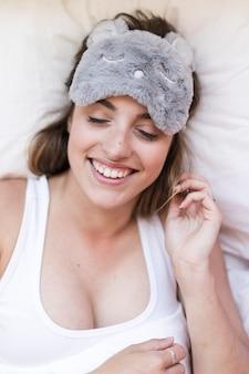 Vista elevada, de, sorrindo, mulher jovem, cama