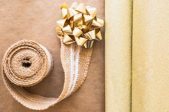 Vista elevada, de, tecendo, fita, e, arco dourado, com, brilhante, papel presente