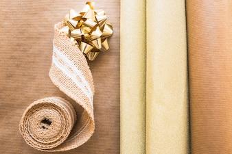 Vista elevada, de, tecendo, fita, e, arco dourado, com, presente, papel, ligado, papel marrom