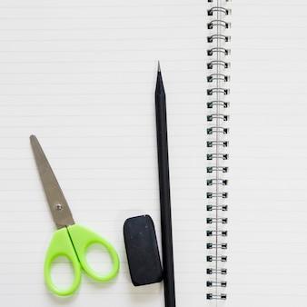 Vista elevada de tesoura; borracha e lápis em caderno espiral