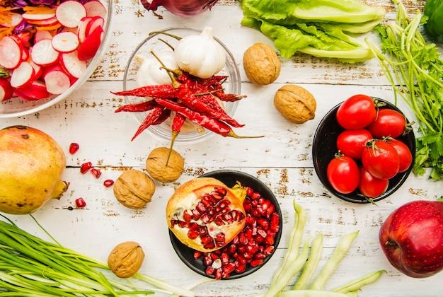 Vista elevada de tomate cereja; pimentões vermelhos; cebolinha; alho; folhas de acelga; salsinha; romã madura e noz