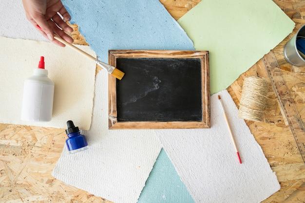 Vista elevada, de, um, mão mulher, segurando, pincel, ligado, deckle, com, papel preto