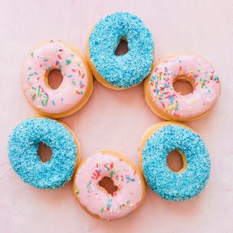 Vista elevada de vários deliciosos donuts no pano de fundo rosa