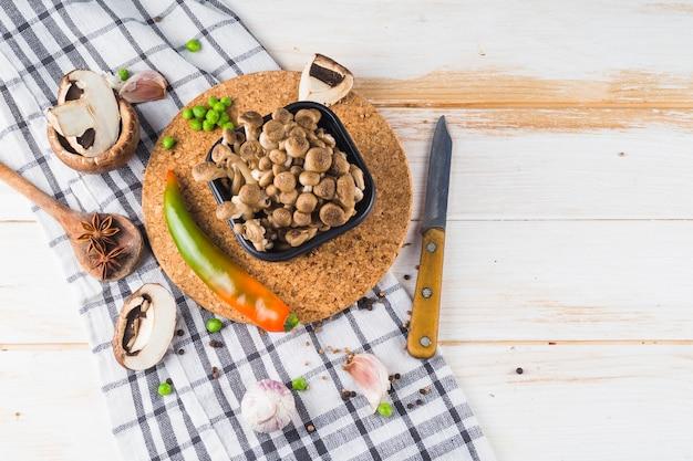 Vista elevada de vegetais; especiarias e utensílio de cozinha na toalha de mesa sobre a mesa de madeira