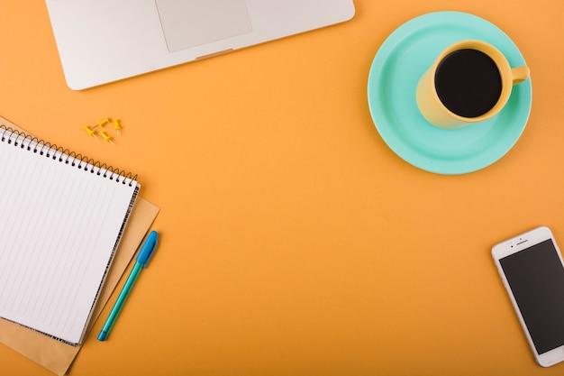 Vista elevada do café preto; smartphone; caneta; pinos de pressão; laptop e bloco de notas em pano de fundo laranja