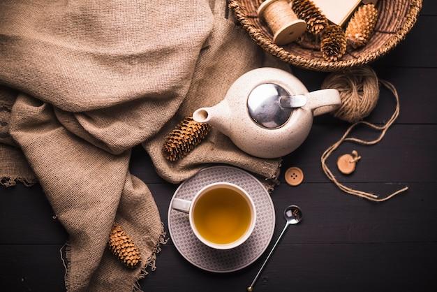 Vista elevada do chá de ervas; pinha; bule de chá; saco; botão; cesta de vime e novelo de lã na mesa