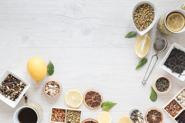 Vista elevada do chá de limão; ervas; filtro; flores secas de crisântemo chinês e toranja seca