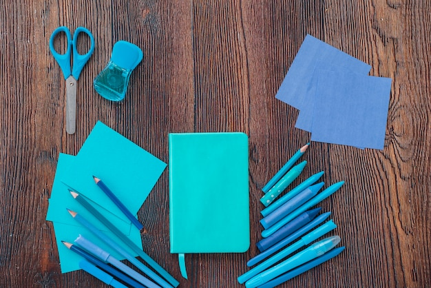 Vista elevada do diário; desenho de cores; tesoura e papéis coloridos na superfície de madeira texturizada
