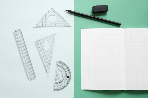 Vista elevada do equipamento geométrico; caderno; lápis e borracha em fundo colorido duplo
