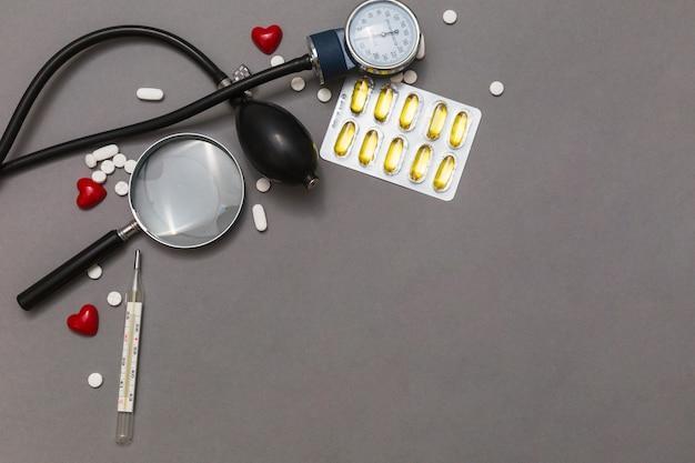 Vista elevada do esfigmomanômetro; lupa; pílulas; termômetro e coração vermelho no fundo cinzento