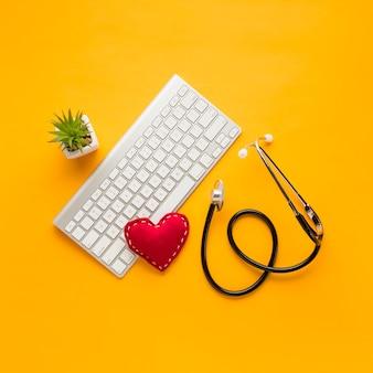 Vista elevada do estetoscópio; forma de coração costurada; teclado sem fio; planta suculenta sobre o pano de fundo amarelo