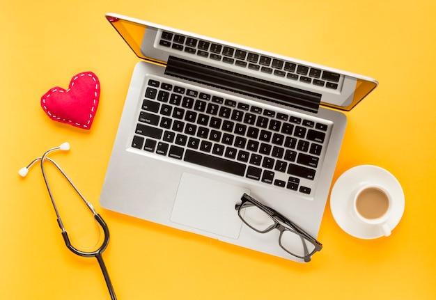Vista elevada do laptop com óculos; coração costurado; xícara de chá e estetoscópio contra fundo amarelo