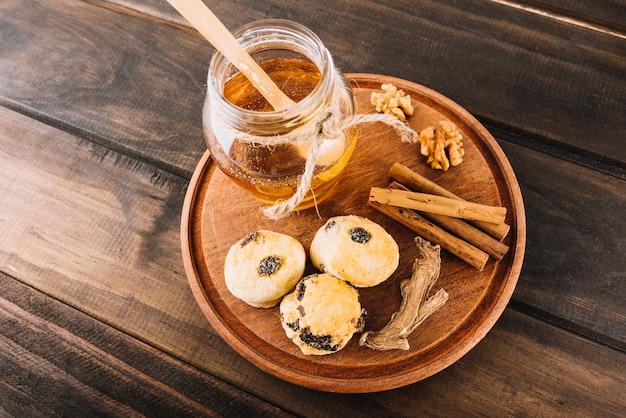 Vista elevada do mel; noz; canela; taça de bolos e gengibre na placa de madeira