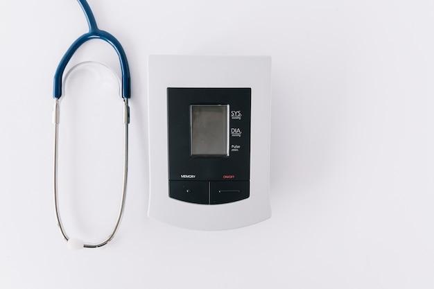 Vista elevada do monitor de pressão arterial e estetoscópio no pano de fundo branco