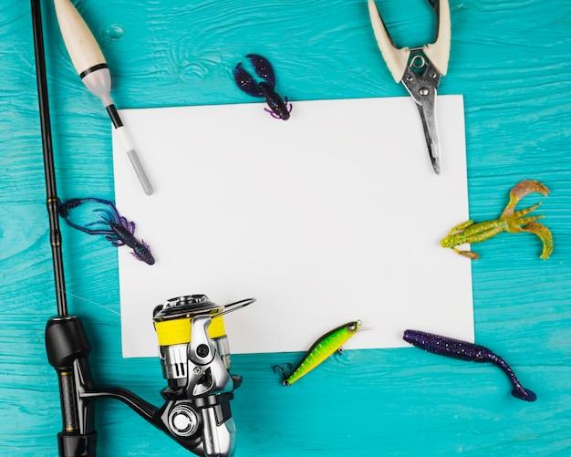 Vista elevada do papel em branco com vários equipamentos de pesca no pano de fundo turquesa