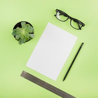 Vista elevada do papel em branco; vaso de planta; lápis; régua e óculos em fundo verde