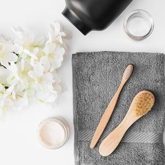 Vista elevada do pincel; toalha; creme hidratante; flores e recipiente em pano de fundo preto