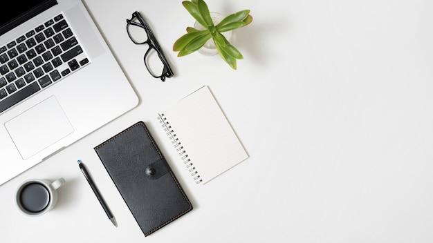 Vista elevada do portátil; xícara de café; diário; óculos e planta em vaso no balcão de negócios