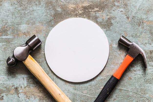 Vista elevada do quadro circular branco entre dois martelos