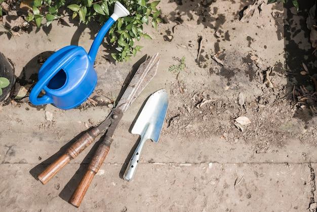 Vista elevada do regador; pá de mão e jardinagem tesoura em estufa