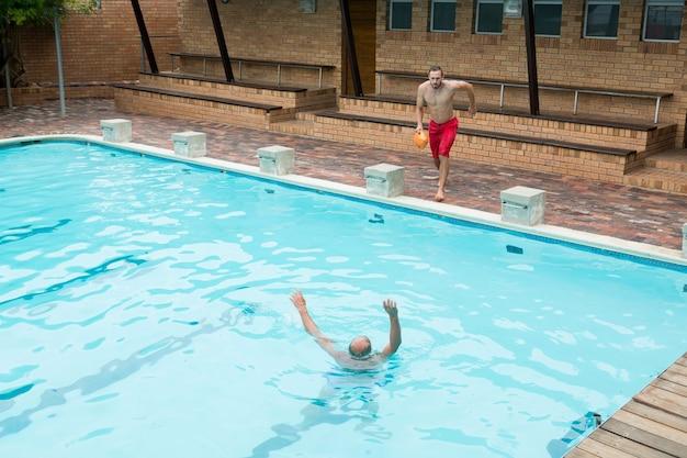 Vista elevada do salva-vidas pulando em uma piscina para resgatar um homem idoso que está se afogando