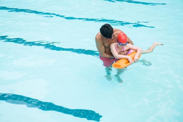 Vista elevada do salva-vidas resgatando menino da piscina
