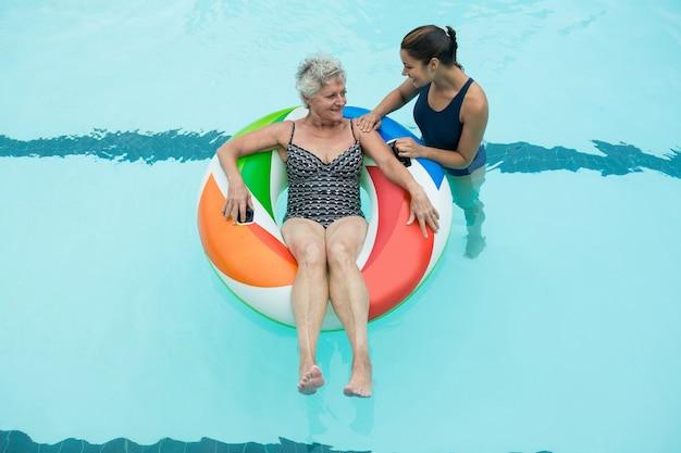 Vista elevada do treinador auxiliando idosa no anel inflável na piscina