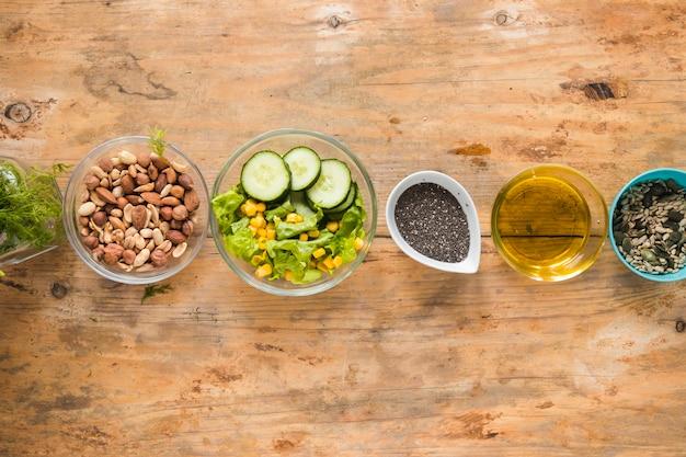 Vista elevada dos dryfruits; óleo; sementes de chia e ingredientes dispostos em uma linha na mesa de madeira