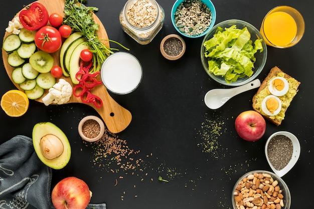 Vista elevada dos ingredientes; dryfruits e legumes em fundo preto
