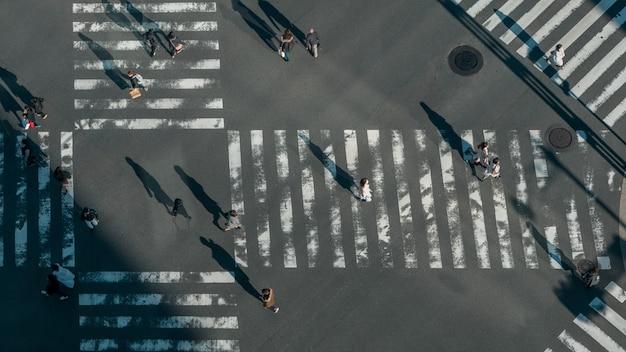 Vista elevada sobre uma multidão de passagem para pedestres japonesa no cruzamento da estrada com a luz de um pôr do sol. vista aérea de asiáticos na movimentada faixa de pedestres do japão.