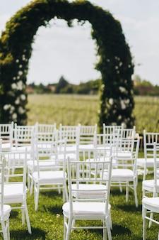Vista em cadeiras brancas e arco antes da cerimônia de casamento