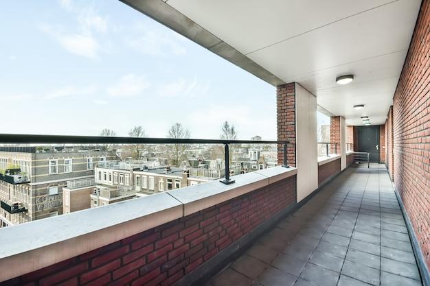 Vista em perspectiva da passagem de azulejos da varanda com parede de tijolos em prédio residencial
