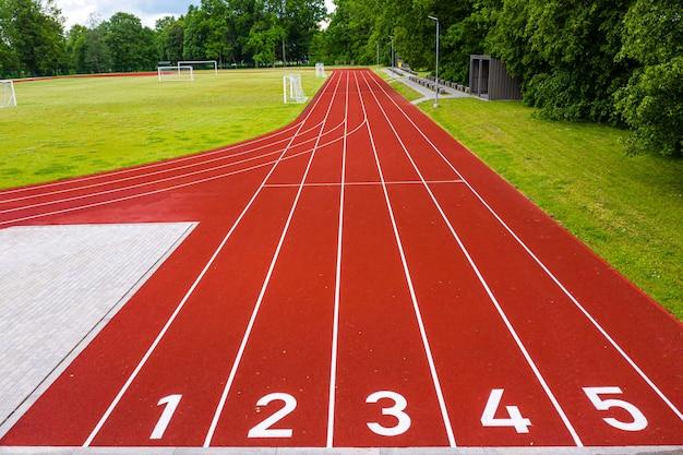 Vista em perspectiva de um estádio ao ar livre com pistas de corrida numeradas em vermelho, infraestrutura para atividades esportivas