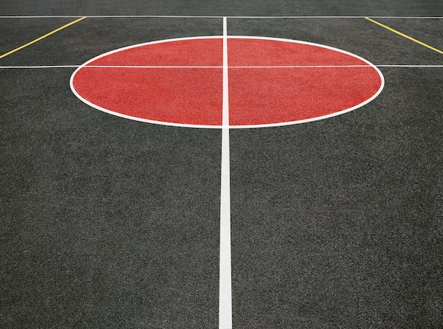 Vista em perspectiva do círculo central do campo de esportes com linhas brancas. campo de jogo preto e vermelho