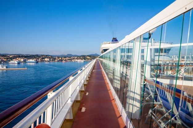 Vista em perspectiva do convés de aço ao ar livre em um navio de cruzeiro com o mar e a cidade ao fundo
