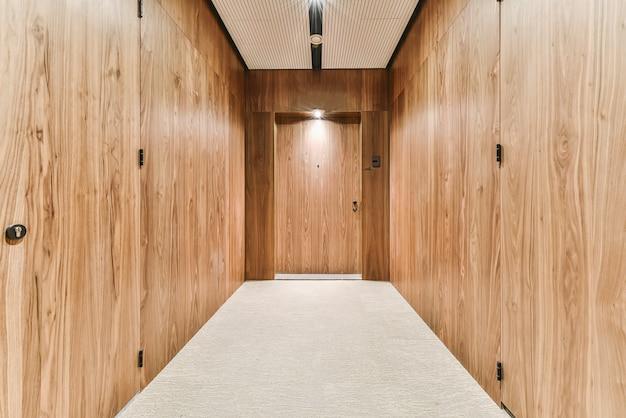 Vista em perspectiva do corredor com paredes em luxuosos painéis de madeira com iluminação suave